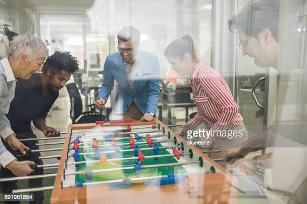 Team of happy entrepreneurs having fun on a break while playing table soccer.