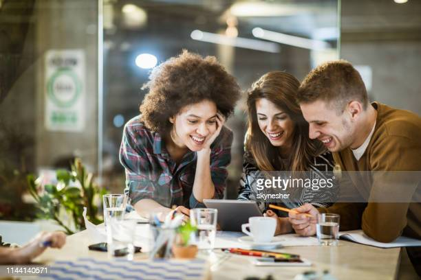 team of happy freelancers using digital tablet in the office. - marketing foto e immagini stock