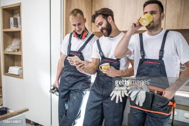 team van gelukkig arbeiders genieten op een koffiepauze. - alleen volwassenen stockfoto's en -beelden