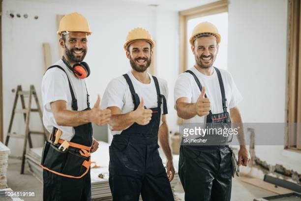 team der glückliche arbeiter daumen auf baustelle auftauchen. - handwerker stock-fotos und bilder