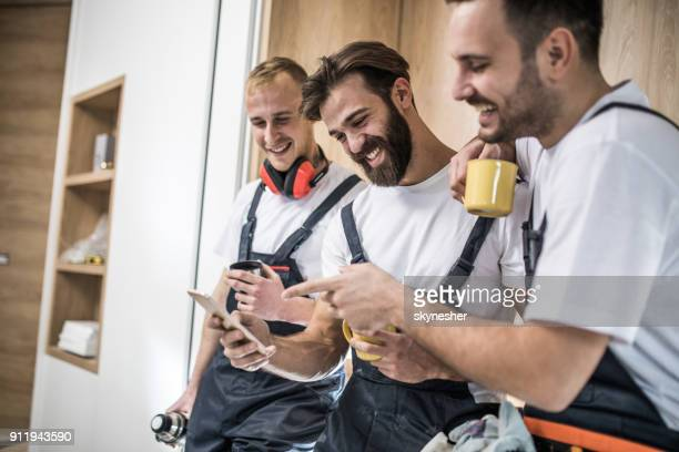 team of happy manual workers using smart phone on a coffee break. - craftsperson stock pictures, royalty-free photos & images