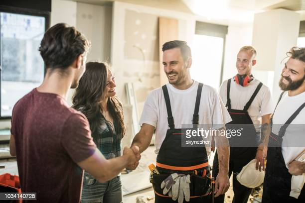 team of happy manual workers welcoming a couple to their apartment. - building contractor stock pictures, royalty-free photos & images