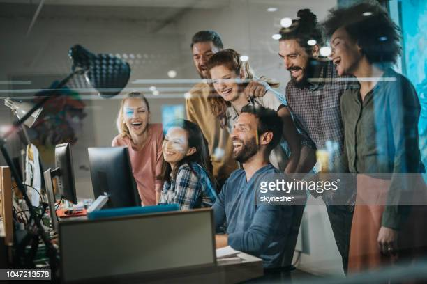 team of happy programmers having fun while working on desktop pc in the office. - casual clothing stock pictures, royalty-free photos & images