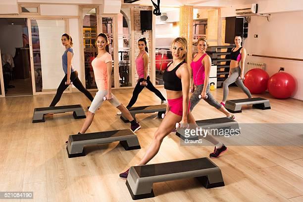Équipe de femmes heureux d'avoir un étape d'aérobic et de poids et haltères.