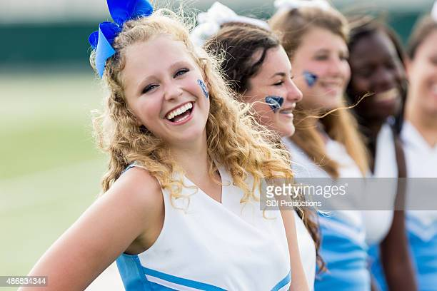 team of high school cheerleaders cheering at sporting event - cheerleaders stock photos and pictures