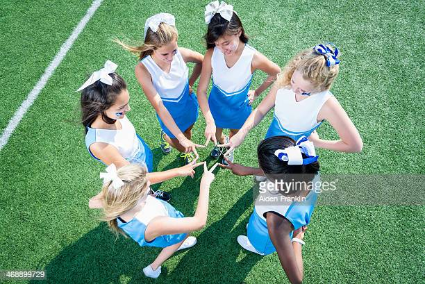 team of high school cheerleaders huddled on sidelines - hair bow stock pictures, royalty-free photos & images