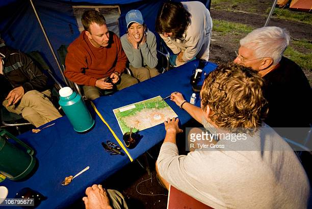 a team of hikers discuss the next day's plans on their way to the summit of mt. kilimanjaro. - mt kilimanjaro stockfoto's en -beelden