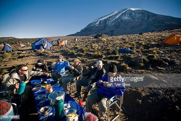 a team of hikers have a nice breakfast at sunrise about 1000 ft. below the summit of mt. kilimanjaro. - kilimangiaro foto e immagini stock