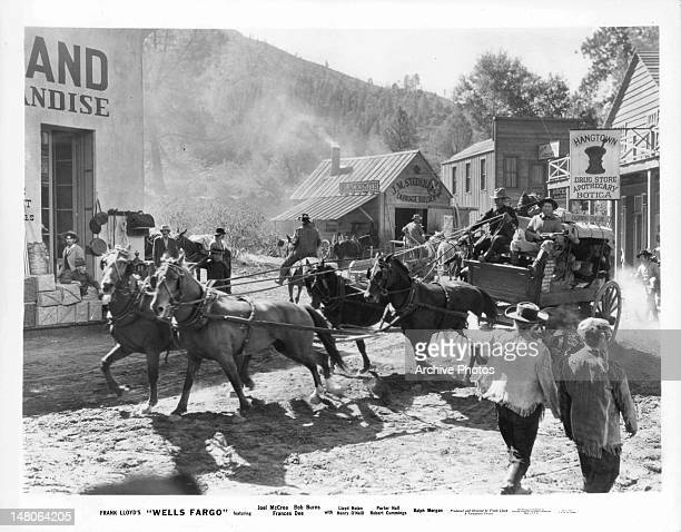 A team of horses are pulling a wagon through town in a scene from the film 'Wells Fargo' 1937