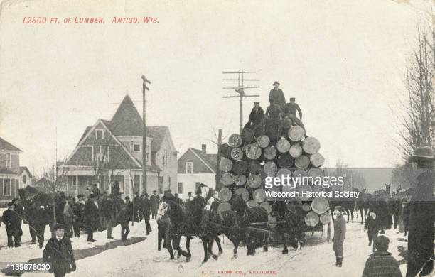 Team of horses driving through Antigo hauling 12800 ft of lumber Antigo Wisconsin 1909 Three men and one driver are sitting on top of the large pile...