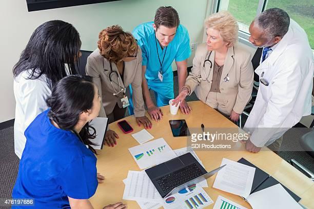 Team of hospital doctors, nurses, and adminstrators in meeting