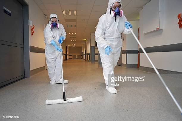 Team of hygienists of the North Hospital of Marseille wearing overalls and masks during the disinfection of the corridors of the new premises with...