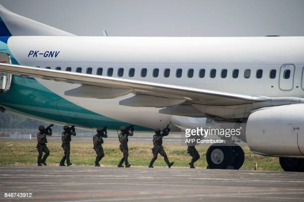 A team of Indonesian antiterror unit move in to storm a hijacked airliner during a demonstration at the Juanda International airport in Surabaya...
