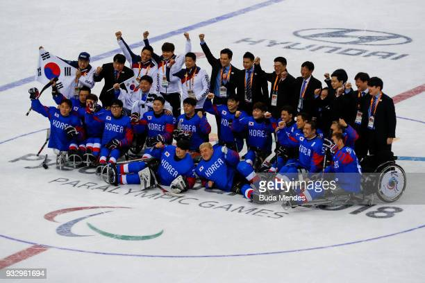 Team of Korea pose for photographers after winning the bronze medal against Italy in the Ice Hockey bronze medal game between Korea and Italy during...
