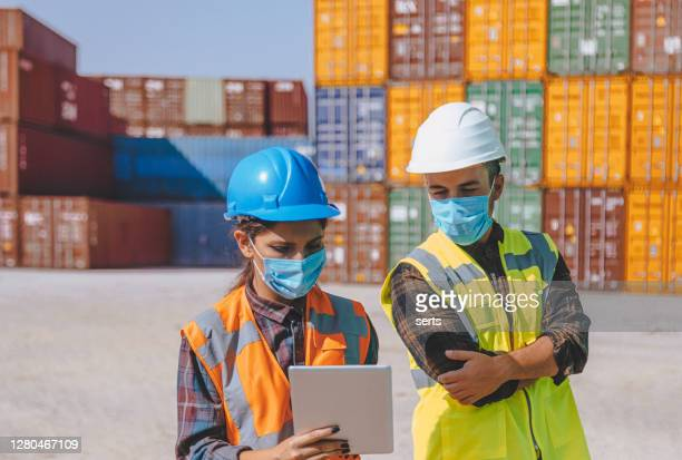 team of logistic engineer man and woman with medical face mask standing outside on a large commercial dock during pandemic - shipyard stock pictures, royalty-free photos & images