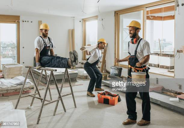 Team of manual workers doing exercises on construction site.