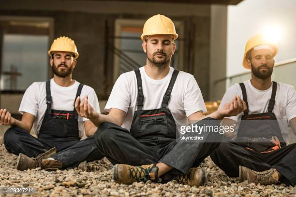 team of manual workers meditating on a terrace of a construction site. - fare una pausa foto e immagini stock