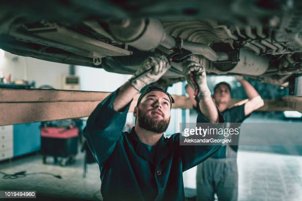 team of mechanics repairing car exhaust system - spoil system stock pictures, royalty-free photos & images