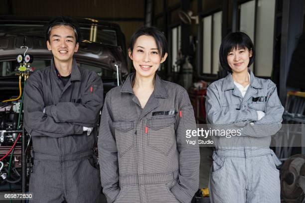 自動車修理工場で作業を行うメカニックのチーム - オーバーオール ストックフォトと画像