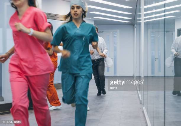 team of medical professionals rush about for emergency in hospital corridor - emergencies and disasters stock pictures, royalty-free photos & images