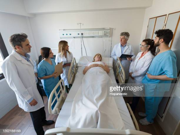 team of medical residents, nurse and senior doctor visiting a senior female hospitalized patient talking to her - civilian stock pictures, royalty-free photos & images