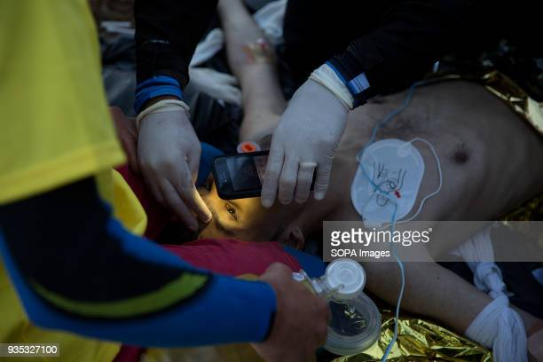 A team of medical volunteers check for signs of life after trying and failing to revive a young Afghan man who drowned off the coast of the Greek...