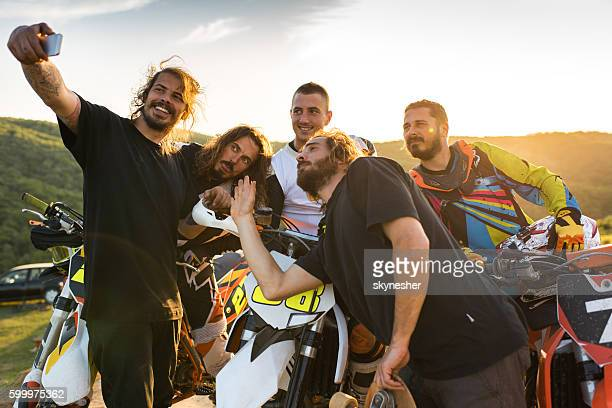 Team of motocross riders having fun and taking selfie.