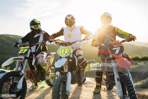 Team of motocross riders on dirt bikes in nature.