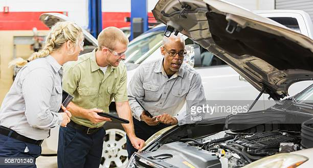 Team of multi-racial auto mechanics working on a car