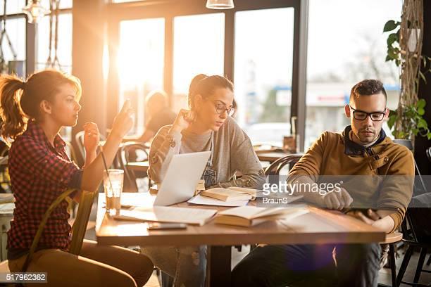 equipe de executar várias tarefas ao mesmo tempo estudantes universitários em um café. - agenda eletrônica - fotografias e filmes do acervo