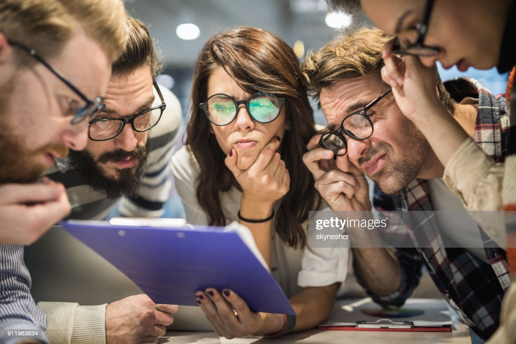Team of nerdy entrepreneurs reading confusing reports in the office. : Stock Photo