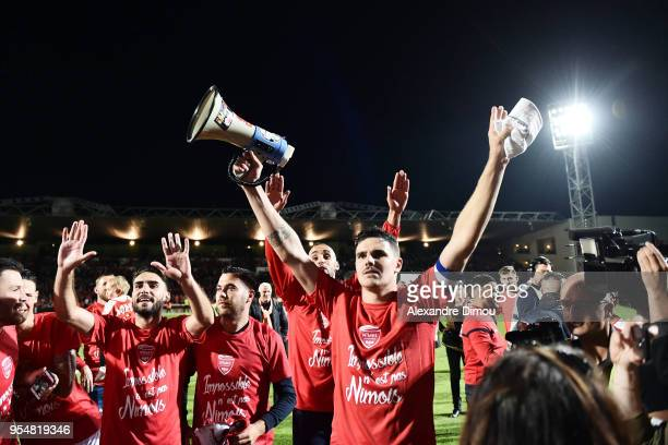 Team of Nimes celebrate winning promotion to the Ligue1 during the French Ligue 2 match between Nimes and Gazelec Ajaccio at Stade des Costieres on...