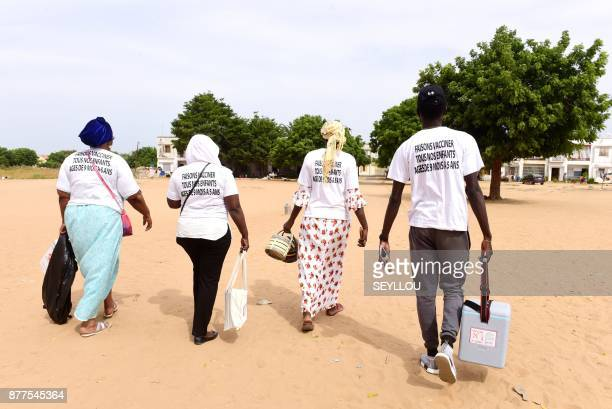 A team of nurses and a community volunteer perform house to house visits in Dakar on November 22 2017 to administer vaccinations against measles and...