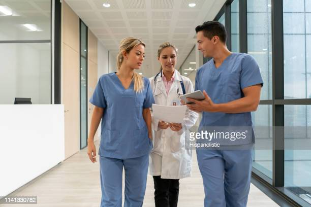 team of nurses talking with doctor while showing something on tablet and walking down the corridor of the hospital - civilian stock pictures, royalty-free photos & images