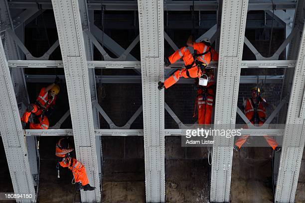 CONTENT] A team of painters and workmen in protective clothing are seeing climbing and abseiling on ropes from the underneath of Blackfriars Bridge...