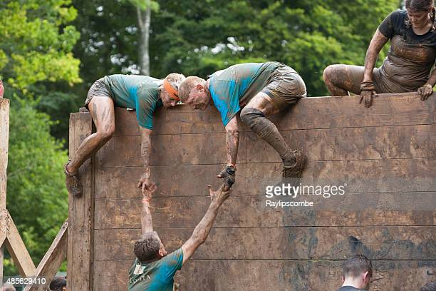 team of people help each other tackle a wooden barrier - obstacle course stock photos and pictures