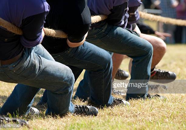Team of people in denim jeans playing tug of war with a rope