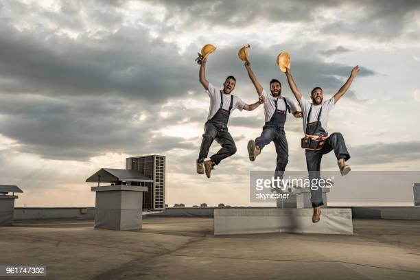 team of playful manual workers having fun while jumping on a roof. - craftsperson stock pictures, royalty-free photos & images