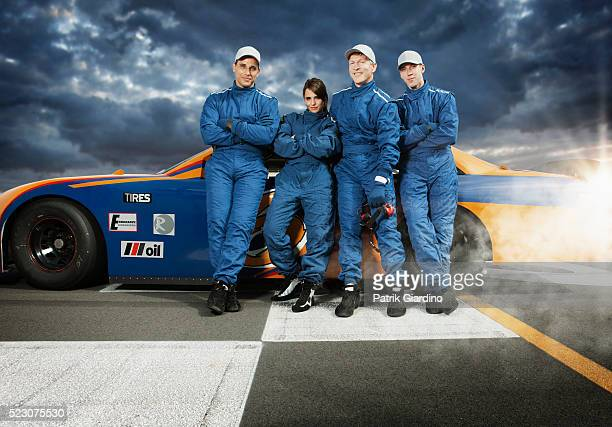 team of race car drivers leaning against racecar - racing driver stock pictures, royalty-free photos & images