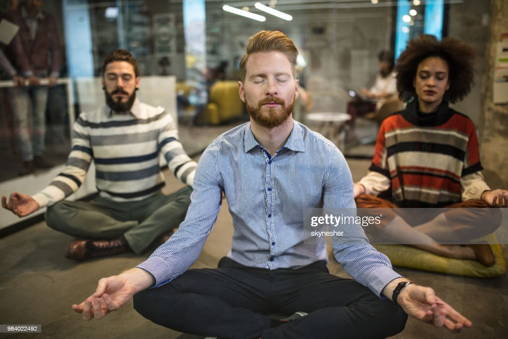 Team of relaxed business people exercising Yoga at casual office. : Stock Photo