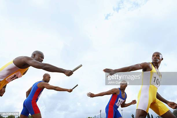 team of relay runners racing against each other - passing sport stockfoto's en -beelden