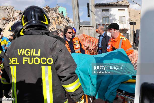 Team of rescuers carry a victim of the earthquake from the rubble to an ambulance on April 6, 2009 in Onna, Italy. The 6.3 magnitude earthquake tore...