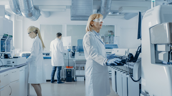 Team of Research Scientists Working On Computer, with Medical Equipment, Analyzing Blood and Genetic Material Samples with Special Machines in the Modern Laboratory. 1140779754