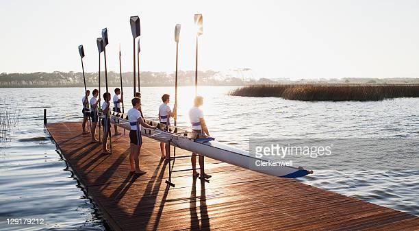 team of rowers standing with canoe on pier - mannschaftssport stock-fotos und bilder
