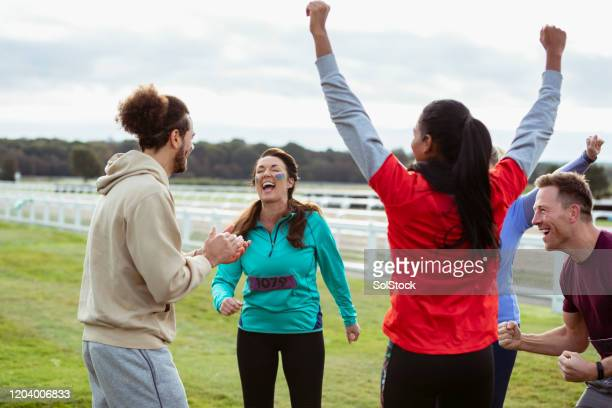 team of runners cheering together at outdoor event - outdoor pursuit stock pictures, royalty-free photos & images
