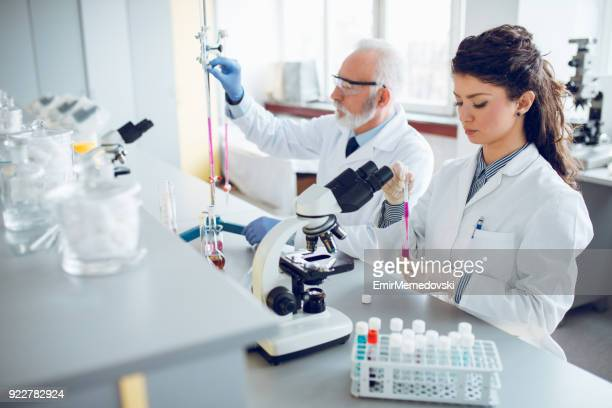Team of scientists in research laboratory conducting science experiments