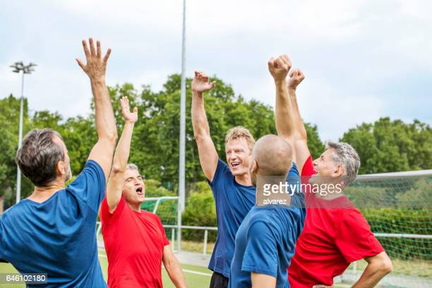 Team of senior soccer players cheering