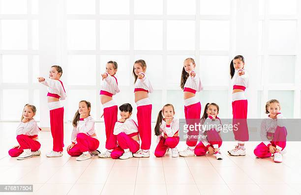Team of smiling little girls dancers looking at camera.