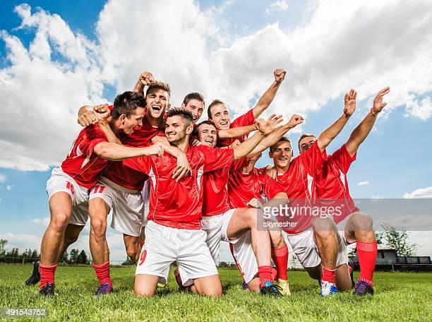 Team von Fußballer feiert auf dem Sportplatz.