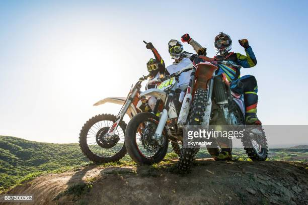 Team of successful motorcyclist on top of the hill.